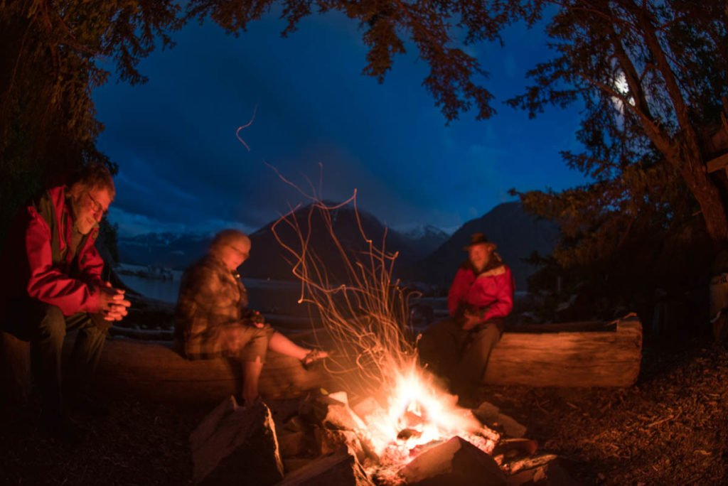 participants relax around campfire after a day at our creative photography workshop in Bella Coola BC Canada